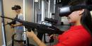 Une jeune femme chinoise joue avec un faux fusil mitrailler en portant un casque de réalité virtuelle dans une salle de jeu à Xingyang en Chine, juillet 2016