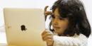 Un petite fille regarde une tablette tactile iPad d'Apple en may 2010