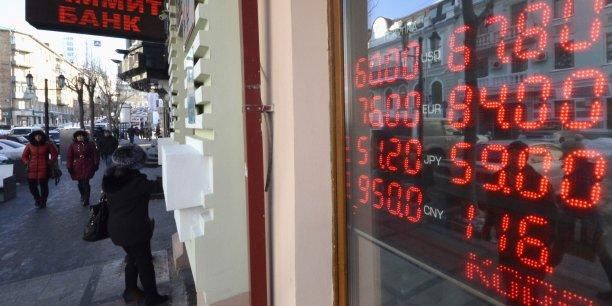 Le rouble, frappé par les sanctions occidentales contre la Russie et la chute du prix du pétrole, a perdu plus de 40 % contre l'euro et plus de 60 % par rapport au dollar. Ici, des panneaux électroniques indiquant les taux, devant un bureau de change moscovite.