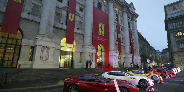 """La place jouxtant la Bourse avait été, pour l'occasion, décorée des symboles de la maison automobile: le célèbre """"cavallino"""" (""""petit cheval"""") cambré et les drapeaux rouges de la marque, ainsi qu'une dizaine de modèles de la voiture de luxe, dont la toute dernière F12 Tdf (ici, en jaune, en partie masquée par deux autres Ferrari)."""