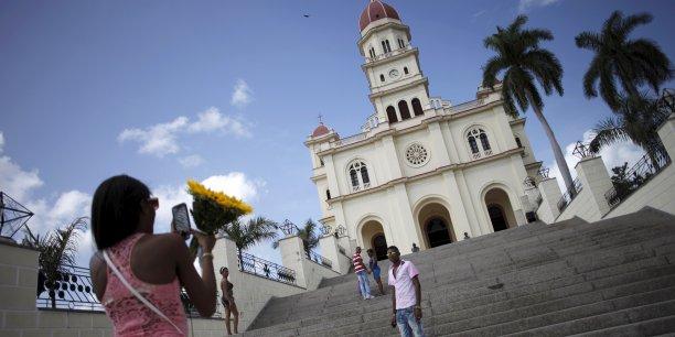 En raison de l'embargo imposé par les Etats-Unis à Cuba depuis cinquante ans, l'île n'avait qu'un accès satellitaire à Internet jusqu'à l'arrivée en février 2011 d'un câble sous-marin de fibre optique installé par son allié politique le Venezuela.  Photo: sur les marches de la basilique Notre-Dame-de-la-Charité, à Cobre, près de Santiago de Cuba, au sud de l'île, le 18 septembre 2015.