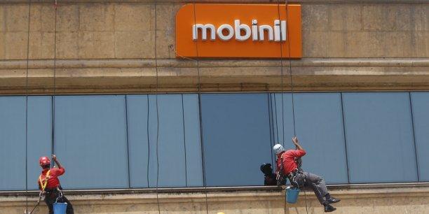 """Des ouvriers lavent les vitres du siège de Mobinil au Caire, en juin 2013. Le logo actuel va bientôt disparaître au profit de """"Orange Egypt""""."""
