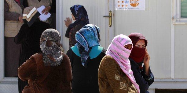 En Jordanie, dans le camp de Al Zaatari, des femmes réfugiées de Syrie attendent de rencontrer un médecin devant le baraquement des consultations médicales.