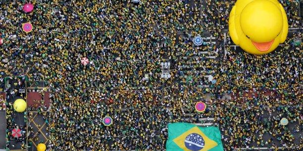 """Bon nombre de Brésiliens reprochent à Dilma Rousseff d'avoir fait plonger l'économie du pays, la principale d'Amérique latine, dans sa pire récession en 25 ans. De manifestation en manifestation le canard en plastique est devenu le symbole du refus de payer la note de cette débâcle (à partir du slogan """"I will not pay the duck, littéralement """"Je ne payerai pas le canard"""", soit """"Je n'essuierai pas les plâtres"""").."""
