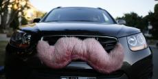 Une voiture arbore la moustache rose, le logo de Lyft.