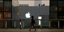 Une femme marche devant un Apple Store à Pékin en Chine en juillet 2016