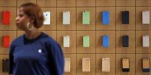 Une employée d'un Apple Store se tient devant un rayon d'iPhone à New York en juillet 2016