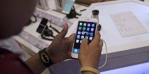 Un homme inspecte un iPhone 6 Plus dans un magasin d'électronique à Bombay, en Inde.
