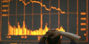 Un homme dépité devant des cours de Bourse à Changchun, province de Jilin en Chine en juin 2008. Crise financière, marchés, effondrement des Bourses