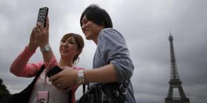 Touristes asiatiques à Paris devant la Tour Eiffel