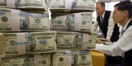 Des employés d'une banque travaillent près d'une pile de billets de monnaie américaine (le dollar) / Argent