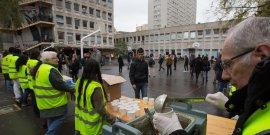 Des bénévoles distribuent des portions de nourriture à des migrants et demandeurs d'asiles dans la cour du lycée Jean Quarre dans le 19e arrondissement de Paris, en octobre 2015