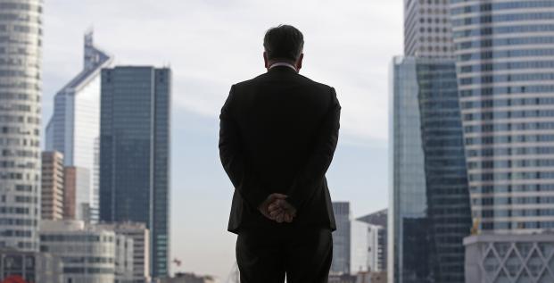 Un homme d'affaires (cadre ou dirigeant peut-être même patron) se tient debout devant l'Arche de la Défense dans le quartier des affaires de Paris en novembre 2012