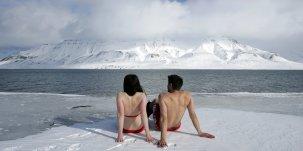 Les activistes du climat Lesley Butler et Rob Bell prennent un bain de soleil sur la banquise arctique norvégienne le 25 avril 2007