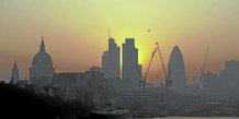The sun rises above the financial district of the City of London April 23, 2011. Britain's Department for Environment, Food and Rural Affairs has issued a smog alert for England and Wales over the Easter weekend, due to high levels of ozone and particulates brought on by summer-like weather conditio