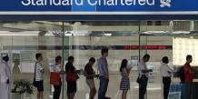Menacée d'une sanction financière de plusieurs centaines de millions de dollars, la banque Standard Chattered fait face en outre des résultats semestriels décevants.