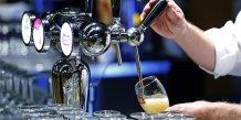Un serveur serrt une bière pression Inbev dans un verre Stella Artois à Bruxelles
