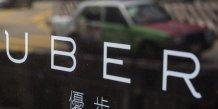 Logo Uber avec un taxi en arrière plan, à Hong Kong en Chine en août 2015 (VTC)