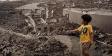 Un enfant japonais passe devant une photographie de la ville d'Hiroshima après le bombardement par une bombe atomique, lors d'une exposition au Musée du mémorial de la paix d'Hiroshima (Japon). Photo prise le 6 août 2007