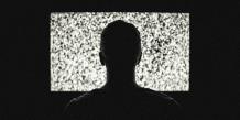 Dos d'un homme qui se tient devant une télévision à l'écran brouillé