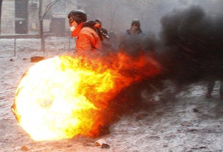 Un manifestant pro-UE s'apprête à lancer un pneu enflammé, le 22 janvier 2014 à Kiev.