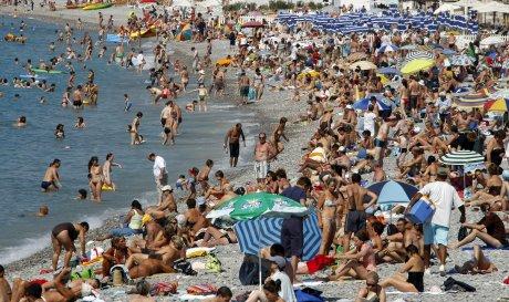 Une plage bondée de touristes  et vacanciers dans le sud de la France à Nice pendant les vacances d'été; Foule population natalité croissance