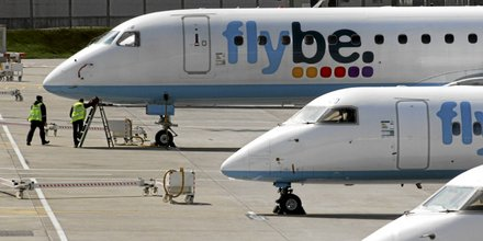 Airline ground crew work on a stationery Flybe aircraft as it sits on the tarmac at Birmingham International airport in Birmingham, U.K., on Tuesday, April 20, 2010. European airspace that was closed by the volcanic eruption in Iceland gradually reopened to flights today after transport ministers sa