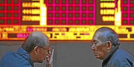 Two men speak in front of an electronic board displaying stock prices at a securities exchange firm in Shanghai, China, on Thursday, Nov. 25, 2010. China stocks rose for a second day after U.S. reports showed employment and consumer sentiment improved, boosting confidence in a global economic recove