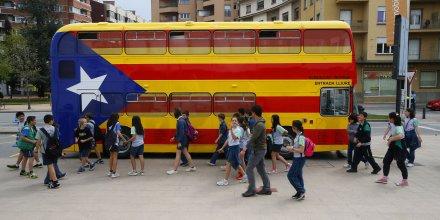 Des étudiants devant un bus aux couleurs du drapeau de la Catalogne