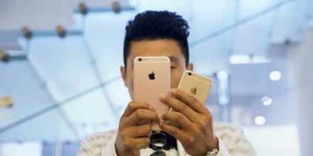 Une homme à Pékin, en Chine, se photographie avec un iPhone 6S et un iPhone 6S Plus le 25 septembre, jour de sortie du dernier smartphone d'Apple