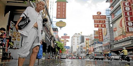 A man gets ready to cross a flooded street in Chinatown in central Bangkok October 29, 2011. Receding floodwaters north of Bangkok have reduced the threat to the Thai capital, the prime minister said Saturday, but high tides in the Gulf of Thailand will still test the city's flood defences. REUTERS/
