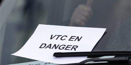 Affichette VTC en danger lors d'une manifestation de chauffeurs LOTI et de VTC, dont Uber France, contre des mesures en faveur des taxis à Paris le 3 février 2016