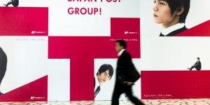 Un Japonais marche devant une publicité pour La Poste japonaise Japan Post