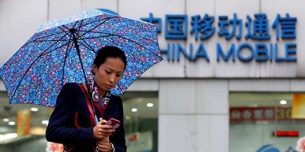 Une femme pianote sur son téléphone à Shanghai, devant une boutique de China Mobile.