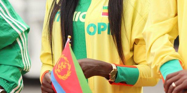 L'athlète éthiopienne Tirunesh Dibaba tient un drapeau érythréen lors d'une cérémonie de bienvenue du ministre érythréen des Affaires étrangères Osman Saleh et de sa délégation à l'aéroport international de Bole à Addis-Abeba, en Éthiopie le 26 juin 2018.