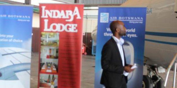 Un steweard accueillant des passagers de Air Botswana sur le tarmac de l'aéroport international de Gaborone.