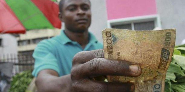 Un commerçant tendant un  billet de naira nigérian dans un marché populaire de la ville de Lagos.