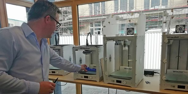 Dans le « fab lab », le directeur général de La Station, Stéphane Deveaux, extrait le logo de La Tribune d'une imprimante 3D.