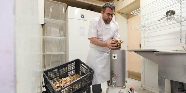 Arnaud Gaset broie le pain invendu pour le transformer en chapelure.