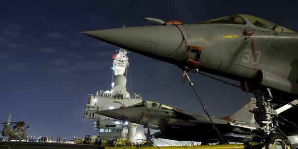 Un porte-avions est un navire de guerre et, s'il peut remplir des missions diplomatiques de présence, il faut, pour que celles-ci soient crédibles, qu'il soit aussi capable d'intervenir militairement, qu'il sache effectivement combattre. (Illustration: photo du porte-avions nucléaire Charles-de-Gaulle prise depuis le pont d'envol avec, au premier plan, sur le côté de la piste d'envol oblique, deux chasseurs Rafale stationnés, petite partie du groupe aéronaval embarqué.)