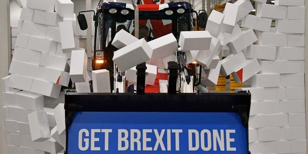 En pleine campagne pour les législatives, Boris Johnson fonce, au volant d'un bulldozer aux couleurs britanniques, vers un mur en briques de polystyrène sur lequel figure le mot impasse.