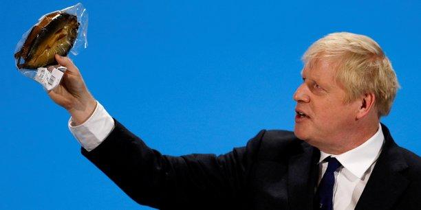 Londres, le 17 juillet 2019. Boris Johnson, alors favori pour le poste de Premier ministre, brandit un hareng fumé dans un emballage plastique pour dénoncer les bureaucrates de Bruxelles qui imposeraient des règles absurdes. Il sera contredit par la Commission européenne.