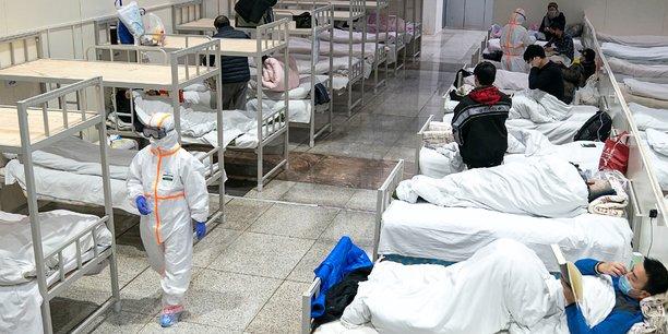 Des personnels de santé en tenue de protection s'occupent des patients au Centre international de conférence et d'exposition de Wuhan, qui a été transformé en hôpital de fortune pour recevoir des patients présentant des symptômes bénins causés par le nouveau coronavirus, à Wuhan, dans la province du Hubei, en Chine (photo prise le 5 février 2020).