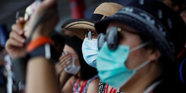 Les organisateurs ont maintenu le salon, mais en prenant des mesures de précaution exceptionnelles. L'accès du grand public a été limité et les participants sont invités à se saluer d'un geste de la main à distance ou en s'inclinant, plutôt qu'en se serrant la main. (Photo de spectateurs assistant à une démonstration aérienne, prise aujourd'hui 11 février, au Singapore Airshow).