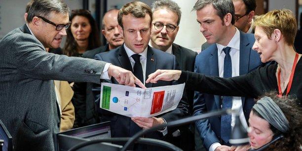 Le président français Emmanuel Macron et le ministre français de la Santé et de la Solidarité Olivier Veran écoutent le professeur Pierre Carli, directeur des services d'urgence SAMU-SMUR de l'hôpital Necker, lors d'une visite au centre d'appels SAMU-SMUR de l'hôpital axée sur l'épidémie de coronavirus COVID-19, à Paris, 10 mars 2020.