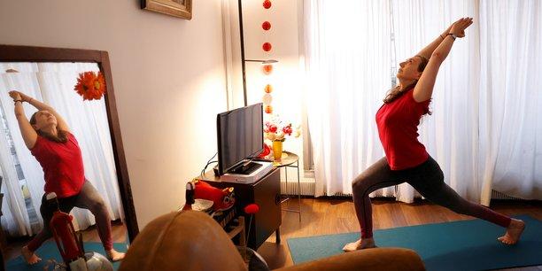 Nombre de salles de gyms sont désormais fermées, alors les accros au sport ou du yoga se tournent vers les cours en ligne pour s'entraîner à domicile.
