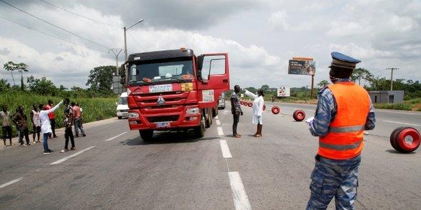 Des agents du ministre de la santé soumettant les camionneurs au contrôle de température à Abidjan, le 30 mars 2020. Les autorités ivoiriennes avaient auparavant réduit le déplacement entre les villes pour limiter la propagation de l'épidémie de coronavirus.