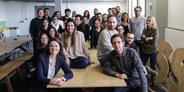 Léa Thomassin, au 1er rang, et une partie de l'équipe d'HelloAsso dans les locaux de l'entreprise à la Cité numérique, à Bègles.