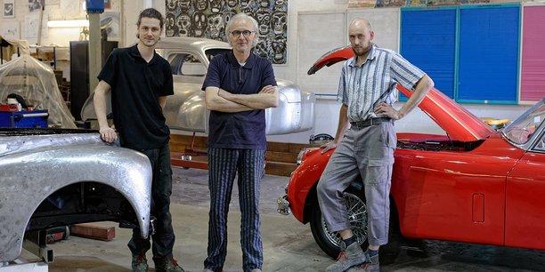 Hubert Haberbusch (au centre), entouré par Romain Gougenot et Isaak Rensing, repreneurs de son entreprise strasbourgeoise de restauration de voitures anciennes.