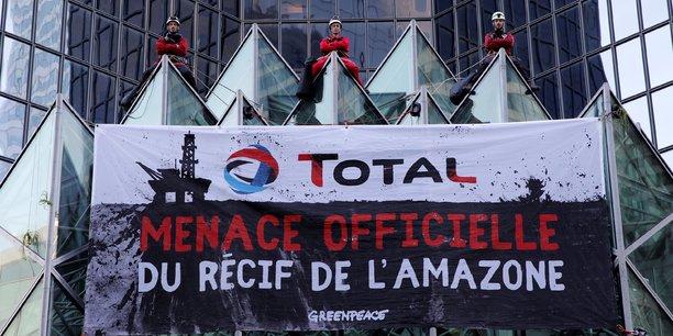 Le 27 mars 2017, des militants de Greenpeace accrochent une banderole qui dit Total, menace officielle du récif amazonien lors d'une manifestation devant le siège du géant pétrolier français Total à La Défense, près de Paris.